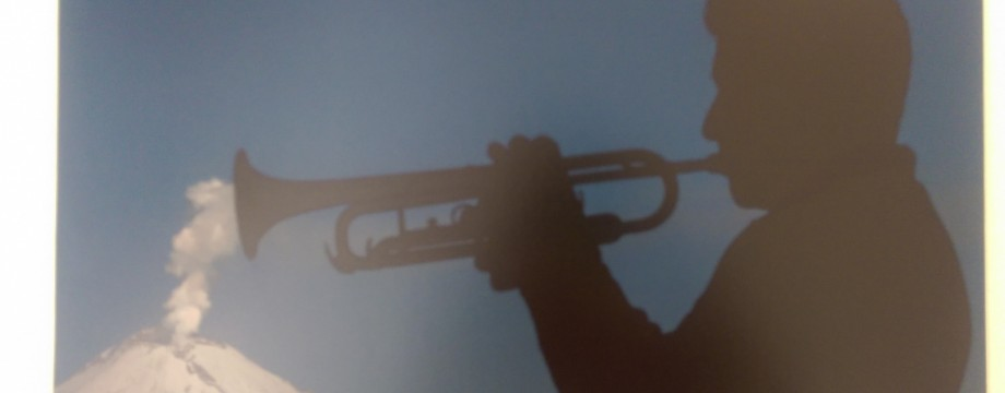 Photo of a trumpet player seemingly sucking smoke from a volcano
