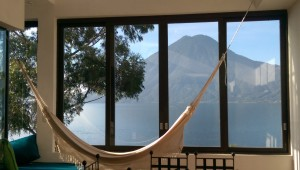 Hammock in front of a window with a view of the volcano behind