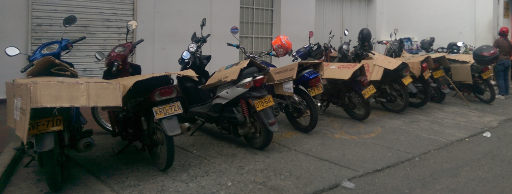 "Motos in a row with cardboard ""covers"" to prevent the seats overheating"