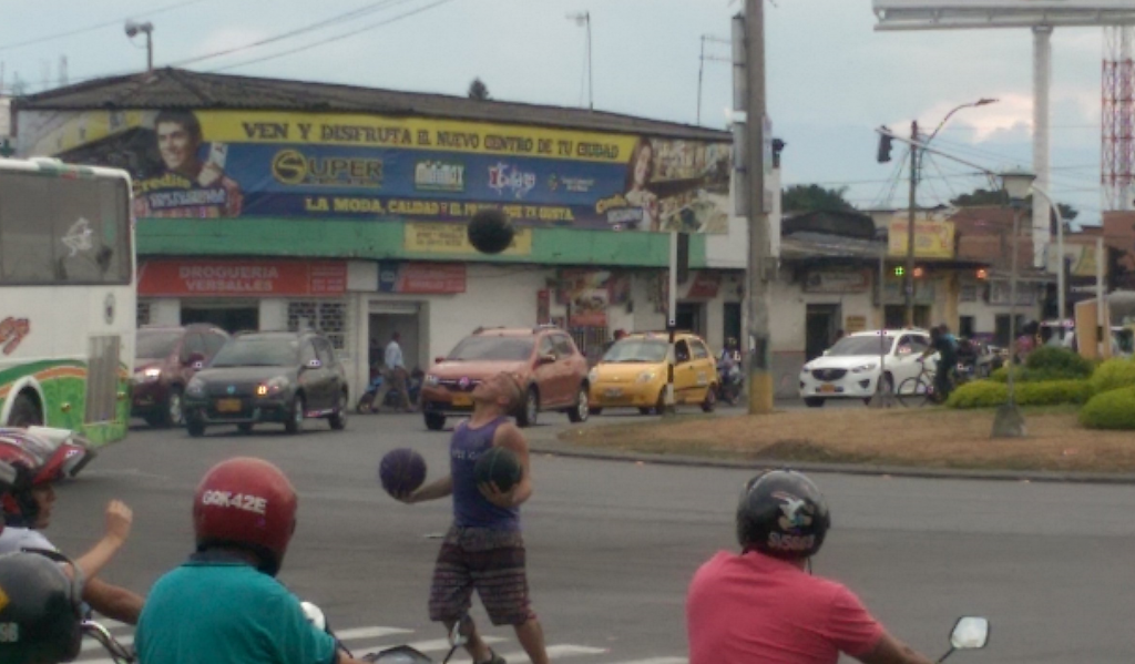 Man juggles balls at traffic lights by Olympica, Versalles, Palmira