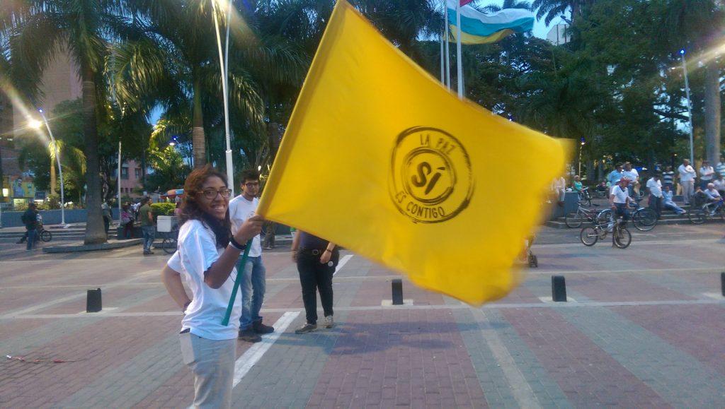 Woman waves Si flag in Parque Bolivar, Palmira